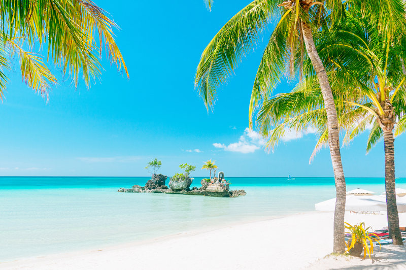 An idyllic scene of palm trees, white sand and aqua waters at Boracay's White Beach in the Philippines.