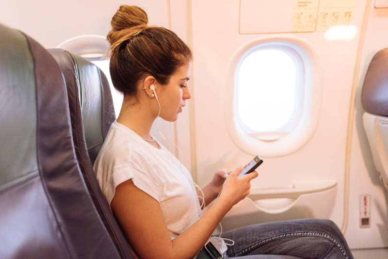 A woman listening to her headphones on an airplane