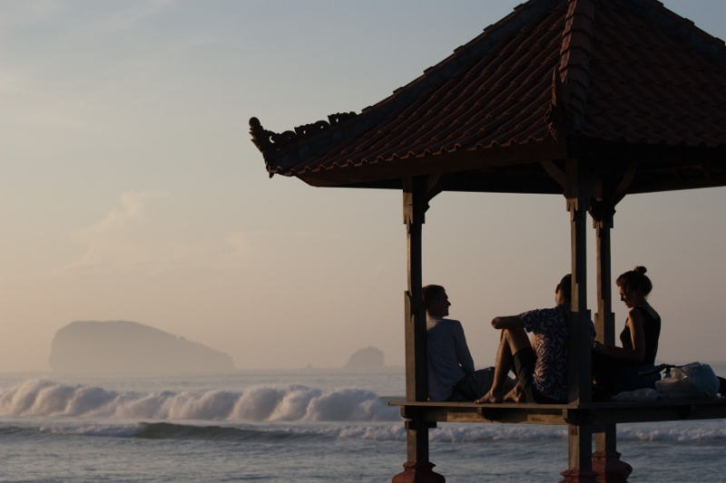 Young people relax in a Balinese pagoda as the waves roll in to Candidasa, Bali.