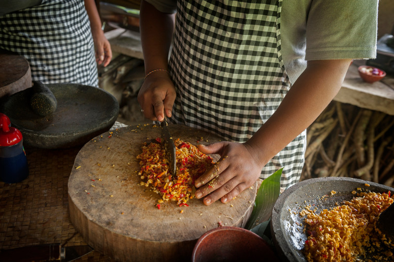 Hands chopping ingredients at a cooking class in Bali, Indonesia.