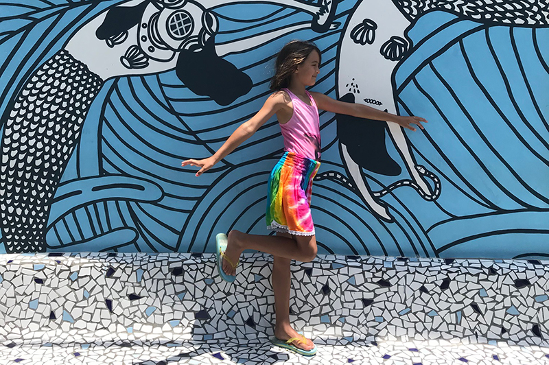 Girl in front of mural in Canggu.