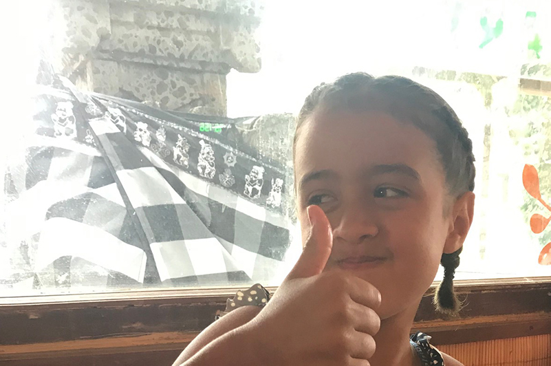 Girl in front of shrine in restaurant, Bali