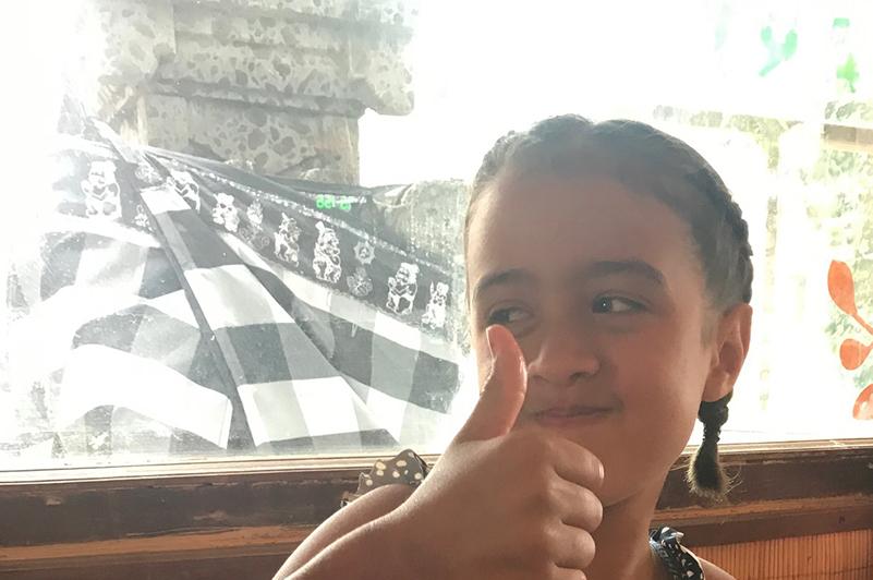 Girl in front of shrine in restaurant, Bali