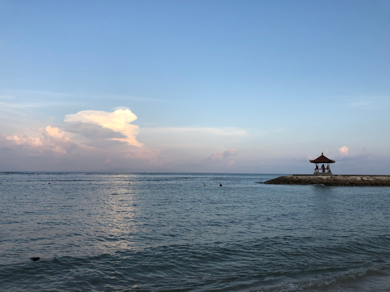Sunset at Nusa Dua Beach with small temple in the background