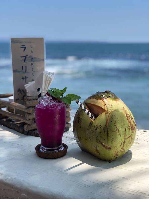 One purple cocktail next to a coconut with ocean in the background