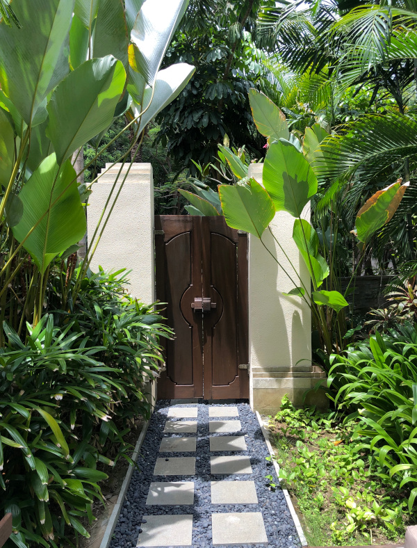 Lush tropical garden with stone pathway leading to a wooden door.