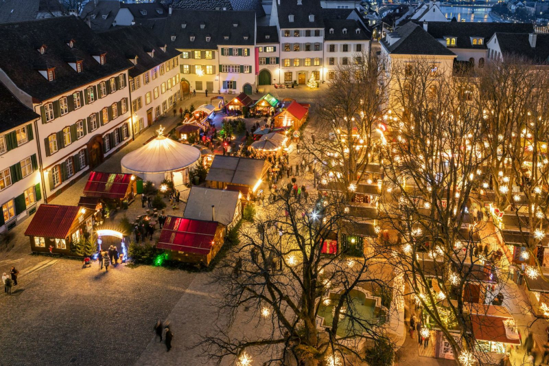An aerial shot of the basel christmas markets. Big light bulbs are hung from trees