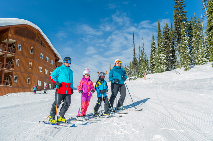 A family of four about to hit the slopes on skis at Big White Ski Resort