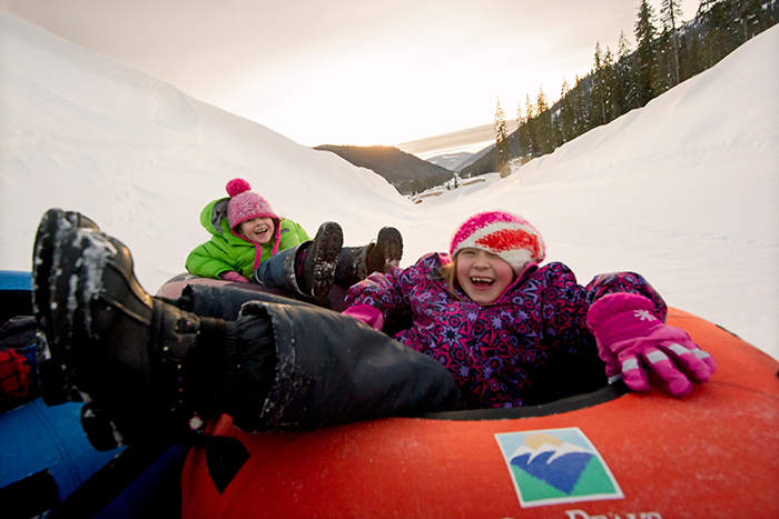 A couple of girls laughing as they tube through Sun Peaks resort