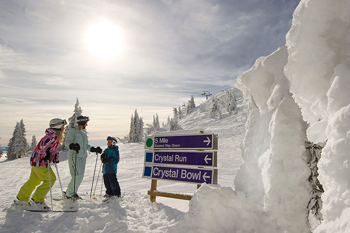 A family in skis standing at directional signs on the ski fields at Sun Peaks Resort