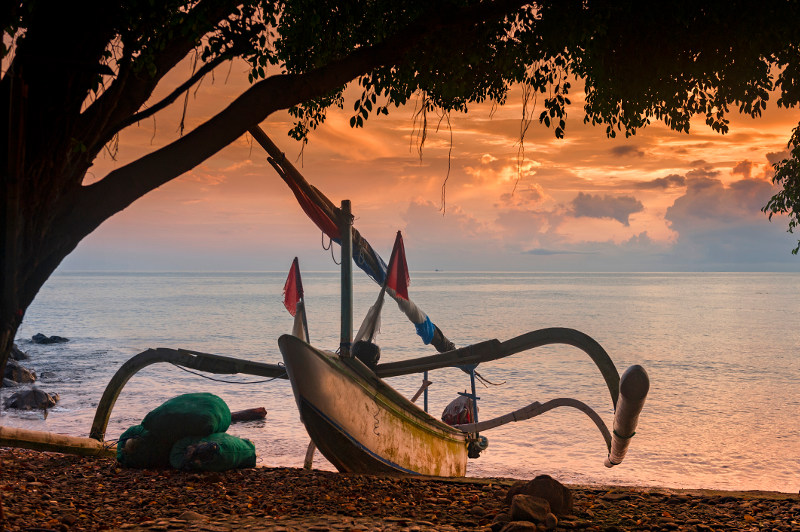 A jukung fishing boat forms an unusual silhouette against the setting sun at Amed Beach in Bali.