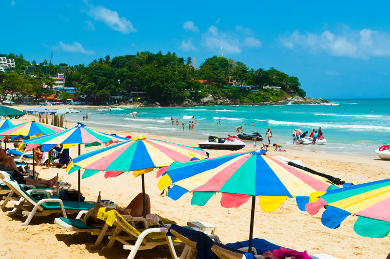 Umbrellas, sun loungers and jet skis dot Kata Beach in Phuket, Thailand.