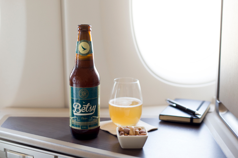 A bottle of Betsy bear and some snacks in a Cathay Pacific aircraft.