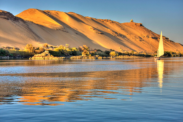 A felucca sails next to sunlit dunes on the River Nile in Egypt - cruise trends to try