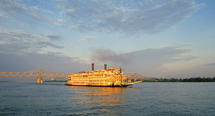 A paddlewheel steamboat cruises down the Mississippi River at sunset with a bridge in background - cruise trends to try
