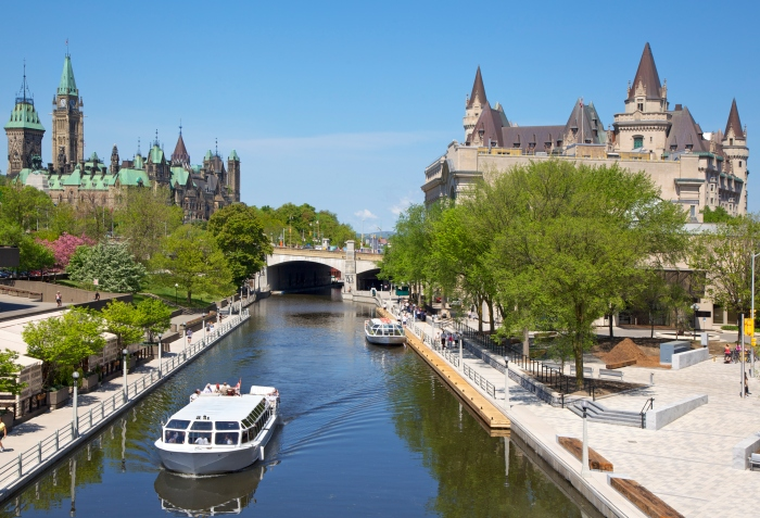 Boats cruise up Rideau Canal next to a park and parliament house - cruise trends to try
