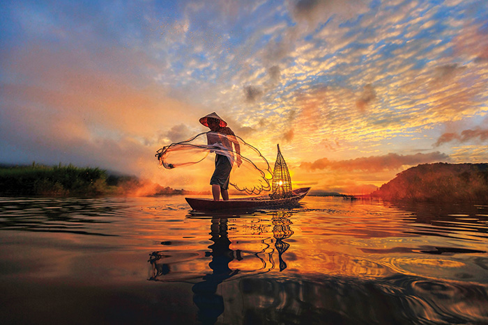A fisherman casts his net at sunrise on the Mekong River, Vietnam - cruise trends to try