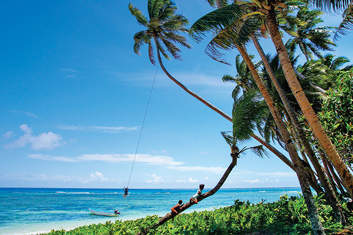 Young kids play in palm trees in Fiji - Cruise trends to try