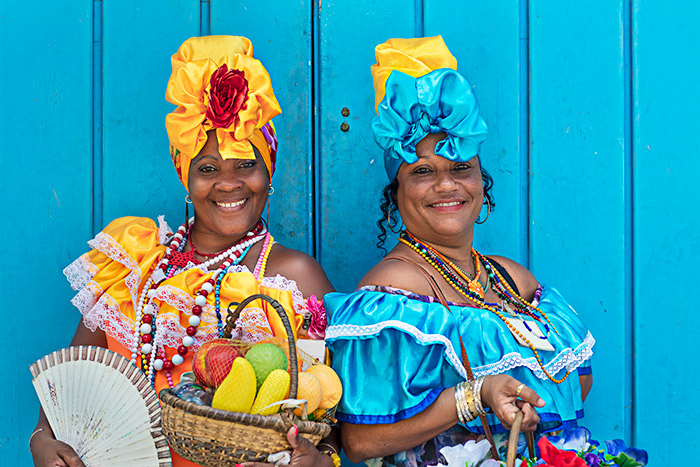 Local Cuban women in colourful traditional dress smile at the camera as they hold baskets of fruit - cruise trends to try.