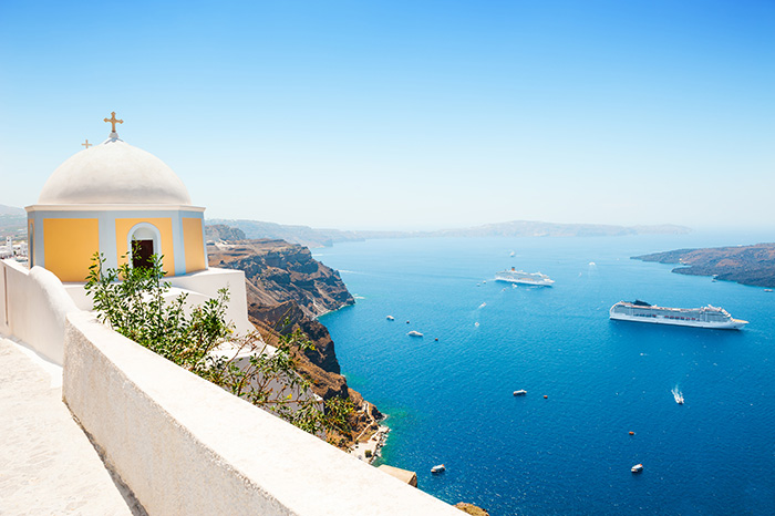 A yellow and white domed church sits on a sheer cliff overlooking passing cruise ships in the ocean below - cruise trends to try