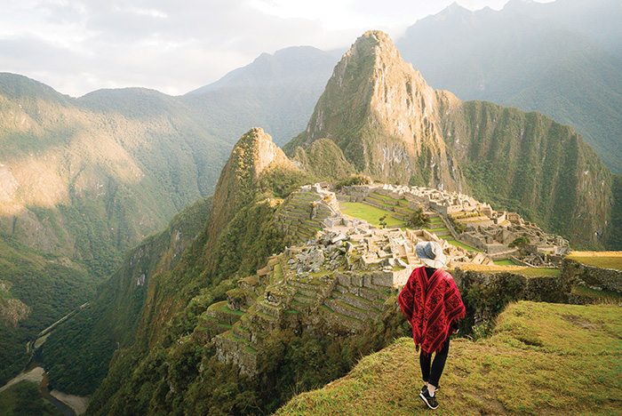 A woman stands in the foreground looking at Machu Picchu and the Inca Trail