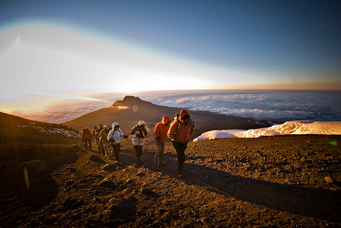 A group of hikers ascend a peak on the Marangu track of Mt Kilimanjaro with the sunrise in the background