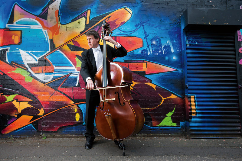 A man plays the cello near a graffiti-covered wall in Birmingham, UK.