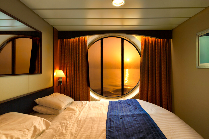 A cruise ship cabin with a porthole looking out to sea.