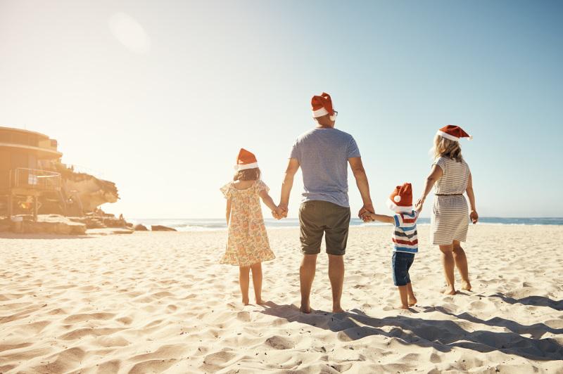 A family at the beach wears Santa hats.