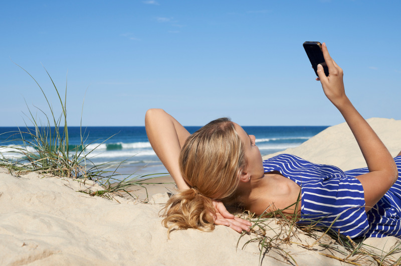 A woman lies back on sand dunes at a beach and looks at her smartphone.