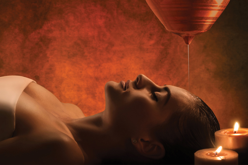 woman laying down with oil running over her head in massage parlour