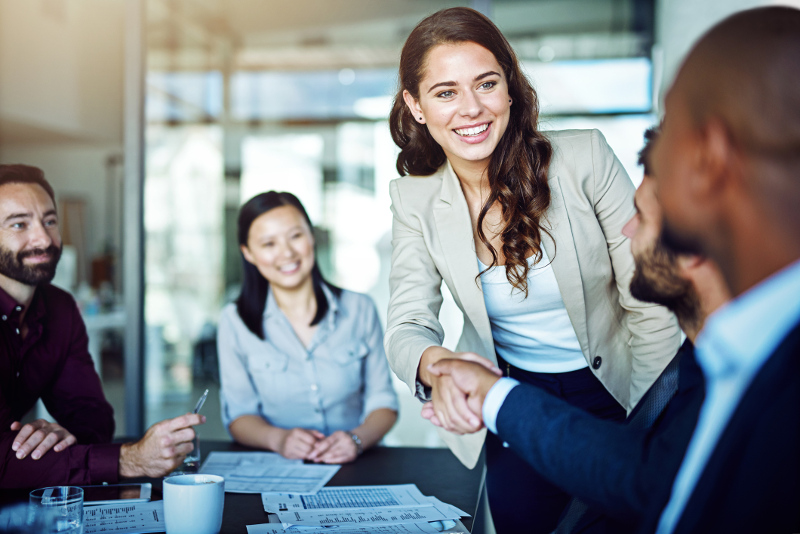 A young professional woman shaking hands with other professionals in a meeting