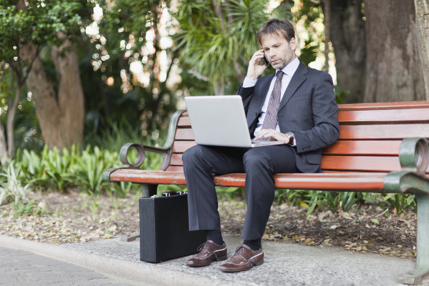 A business man working on a park bench