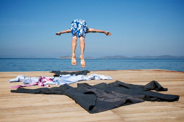 Man diving into water with work clothes on pontoon