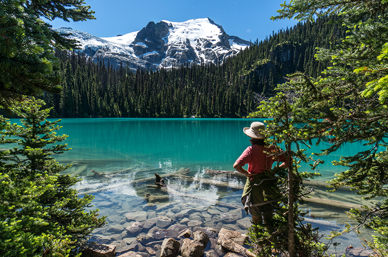 a woman looks over a blue lake in joffre lakes national park