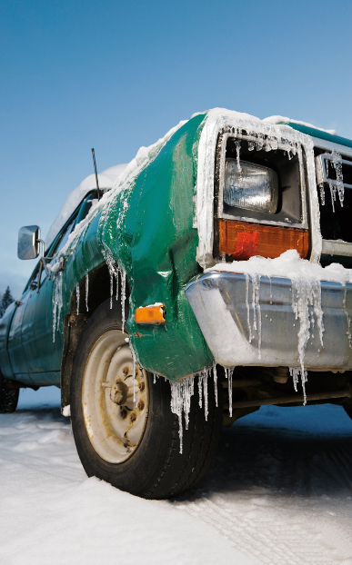 A truck with icicles hanging off the bumper