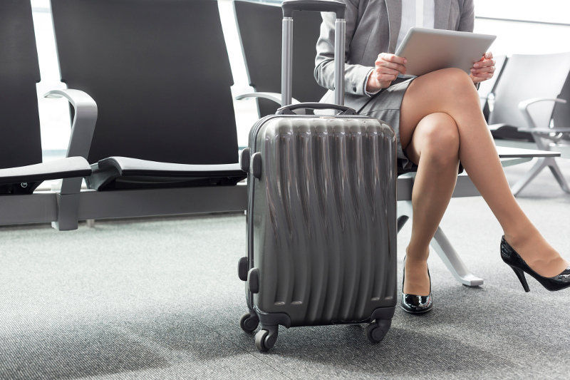 A woman at the airport with her carry-on bag