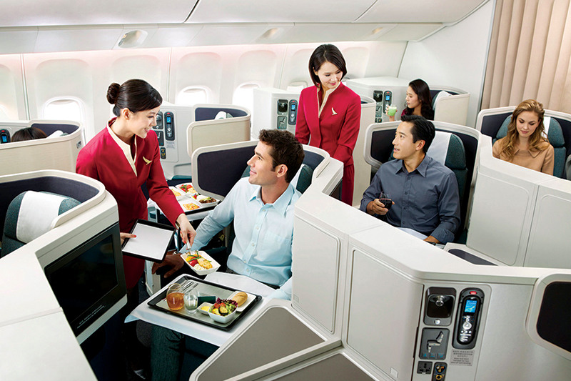 A Cathay Pacific attendant serving a meal