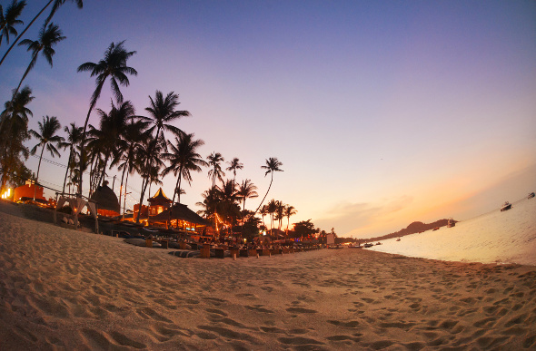 A cafe by the beach as the sun sets in Koh Samui, Thailand.