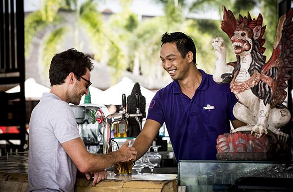 A G.O serves a guest at the bar at Club Med Bali