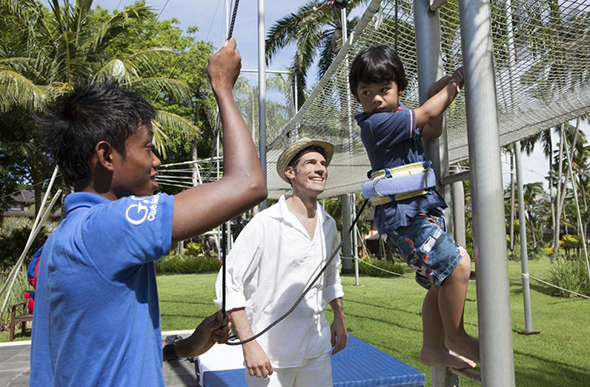 A G.O teaches a young boy how to trapeze