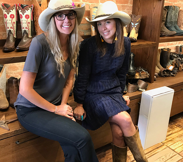 Two women sit in front of cowboy boots at an Aspen store.