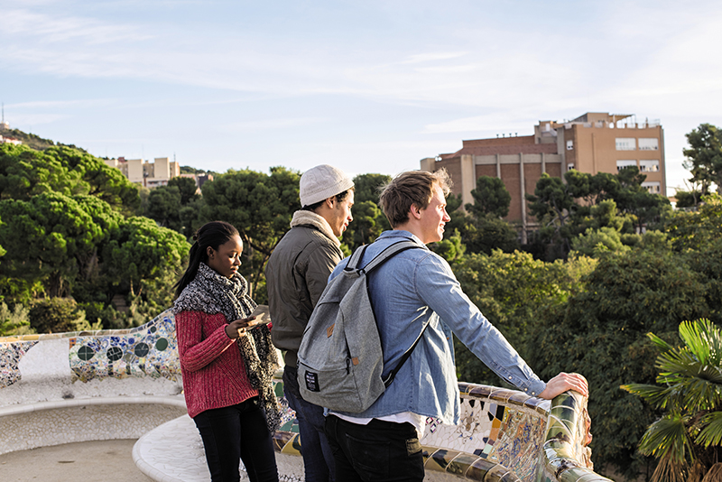 travellers at parc guell lookout in barcelona