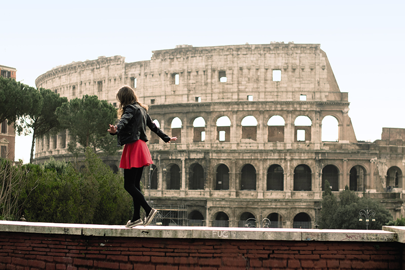 girl walking in front of the colosseum