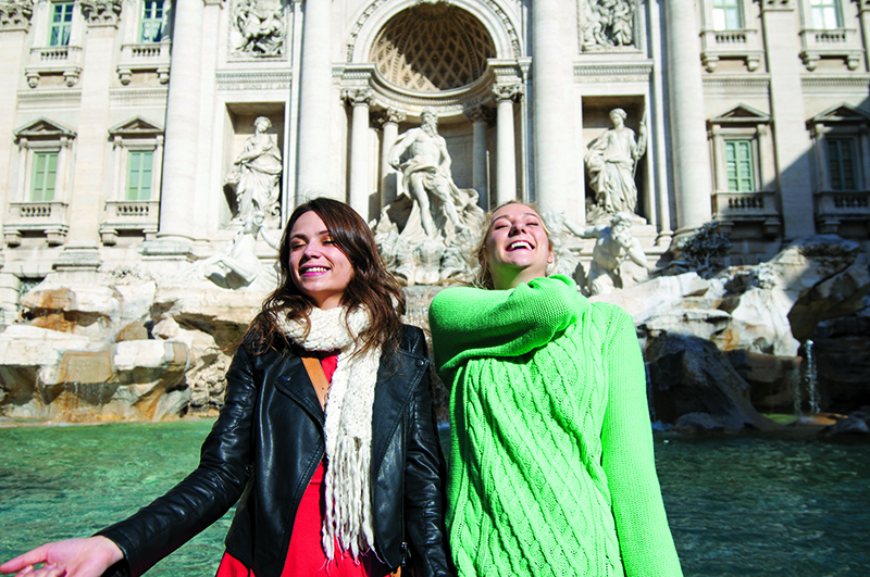two girls throw coins into the trevi fountain