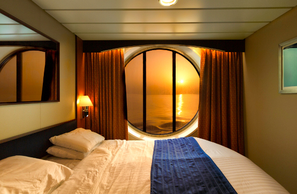 A cruise ship cabin with a window looking out at the ocean