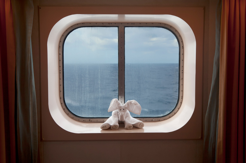 A towel-art elephant sits on a window sill in a cruise ship cabin.