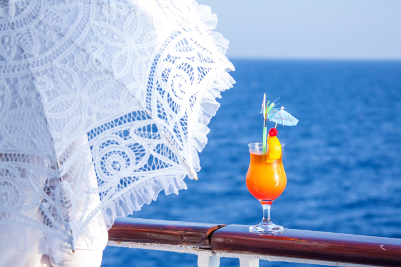 A woman with a parasol rests her drink on a cruise ship's railing.