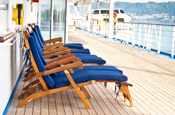 Empty lounge chairs along a cruise ship promenade