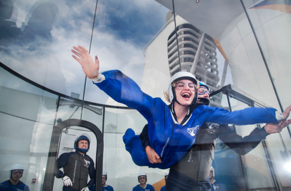 A woman skydives in a wind tunnel on board cruise ship Ovation of the Seas.